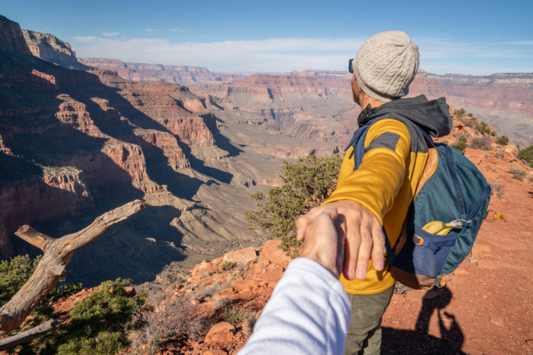 follow-me-to-concept-young-man-leading-girlfriend-to-the-grand-canyon-enjoying-travel-in-the-usa